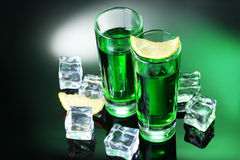 Two glasses of absinthe, lemon and ice. On green background royalty free stock photo