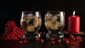 Two glasses with alcohol and ice, decorated with pomegranate, red candle and handmade heart, close-up. Romantic still stock footage