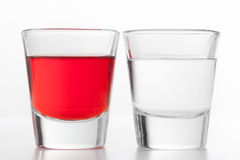 Two glasses of alcohol. One red flavoured, the other clean vodka. Stock Image