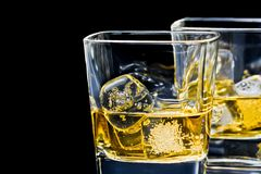 Two glasses of alcoholic drink on black background Royalty Free Stock Photos