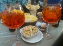 Two glasses of aperol spritz with hors d`oeuvres of green olives, chips and peanuts stock photos