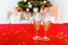Two glasses on the background of Christmas tree with place for text insertion. Stock Image