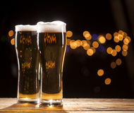 Two glasses of beer on bar lights background Stock Images