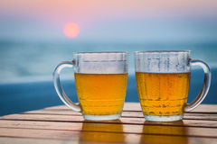 Two glasses of beer on a beach. Sea Royalty Free Stock Image