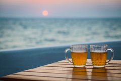 Two glasses of beer on a beach. Sea Royalty Free Stock Photography