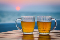 Two glasses of beer on a beach. Sea Stock Image
