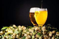 Two glasses of beer flowing Stock Images