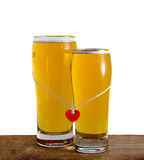 Two glasses of beer for lovers isolated on white. Two glasses of beer for lovers with red heart isolated on white background Royalty Free Stock Photos
