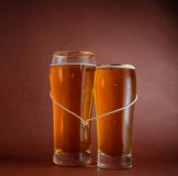 Two glasses of beer for lovers. With key on a string Royalty Free Stock Images