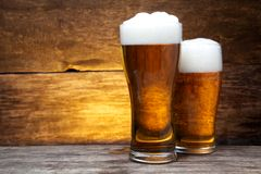 Two glasses of beer over vintage wood Royalty Free Stock Images