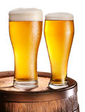 Two glasses of beer over woden barrel. Royalty Free Stock Images