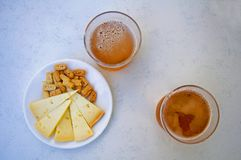 Two glasses of beer and snacks, center, atop stock images