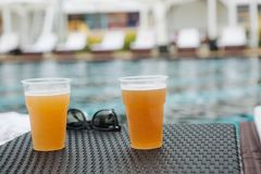 Two glasses beer sunglasses table pool royalty free stock photography