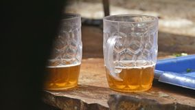 Two glasses of beer on a table outside the slow motion video stock video footage