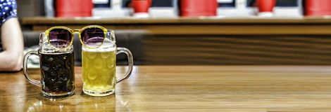 Alcohol, beer, drink, pub, bar, lager, brewery, celebration, closeup, restaurant, table, glass, pint,. Two glasses of beer on the table in a pub with sunglasses royalty free stock image