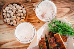 Two glasses of beer, toasted toast with a crust, dill and pistac. Hios on a wooden table. Selective focus on foam, top view Stock Photos