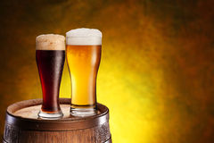 Two glasses of beer on a wooden barrel. Royalty Free Stock Image