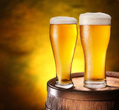 Two glasses of beer on a wooden barrel. Stock Photography