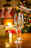 Two glasses being filled with champagne at Christmas eve Stock Photo