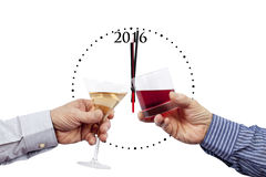Two glasses being raised in front of a 2016 clock. Two new year glasses being raised in front of a 2016 clock past midnight on a pure white background Royalty Free Stock Image