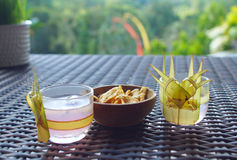 Two glasses of beverage and snack on table Stock Images
