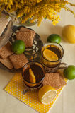 Two glasses of black tea in glass holders, some biscuits, ripe lemons and limes on a linen surface against the light background Royalty Free Stock Image