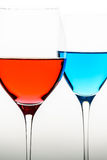 Two glasses with blue colored water and wine Stock Photos