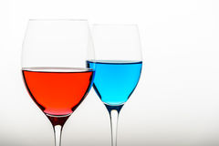 Two glasses with blue colored water and wine Stock Photography