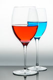 Two glasses with blue colored water and wine Royalty Free Stock Photos