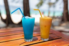 Two glasses with a blue and orange cocktail stand on a wooden table under the rays of the sun. stock photo