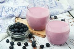 Two glasses with blueberry yogurt. And a bowl with fresh blueberry stock image