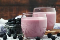 Two glasses with blueberry yogurt. And a bowl with fresh blueberry royalty free stock photos