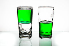 Two glasses, both half-full of green liquid. Stock Images