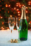 Two glasses and a bottle of champagne is on a festive tablecloth Royalty Free Stock Photography