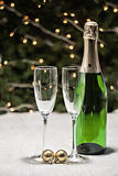 Two glasses and a bottle of champagne is on a festive tablecloth Royalty Free Stock Photo