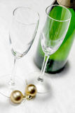 Two glasses, a bottle of champagne and gold Christmas balls clos Royalty Free Stock Photo