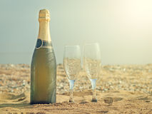 Two glasses and a bottle of champagne on a sandy beach on a hot summer day. A bottle of sparkling wine with glasses on a white plate. Sandy summer beach in the Stock Photo