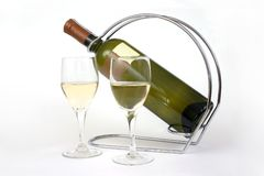 Two glasses and a bottle of wine. Two glasses of wine and a bottle of wine standing in a holder Royalty Free Stock Photo