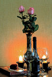 Two glasses with a bottle of wine on the table next to candles Royalty Free Stock Photo