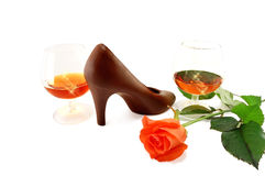 Two glasses of brandy, chocolate slipper and rose Royalty Free Stock Photography