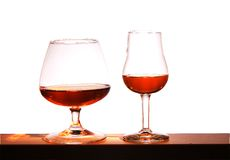 Two glasses with brandy on a white background. Two glasses with brandy on a white bright background Stock Images