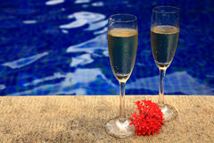 Two glasses of bubbly champagne. At the pool ready for a happy celebration royalty free stock photos