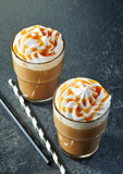 Two glasses of caramel latte with whipped cream royalty free stock images