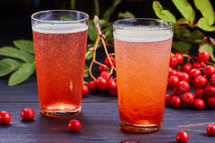 Two glasses of carbonated drink with rowan syrup. Two glasses of carbonated drink with syrup of rowan and fresh rowan berries on dark wooden table Stock Photo