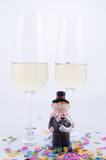 Two glasses with champagne. With confetti and figurines Royalty Free Stock Image