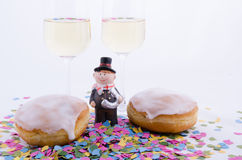 Two glasses with champagne. With confetti and cake and figurines stock photography