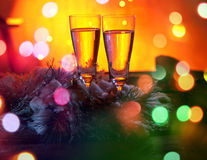 Two glasses of champagne against gold bokeh background. Two glasses of champagne against colorful gold bokeh background Royalty Free Stock Image