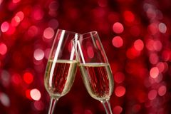 Two glasses of champagne against red background with sparkles. Very shallow depth of field. Selective focus Royalty Free Stock Image