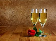 Two glasses of champagne with artificial red rose Royalty Free Stock Photos