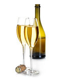 Two glasses of champagne on the background of brown bottles close-up isolated on a white. Festive still life. Royalty Free Stock Photos